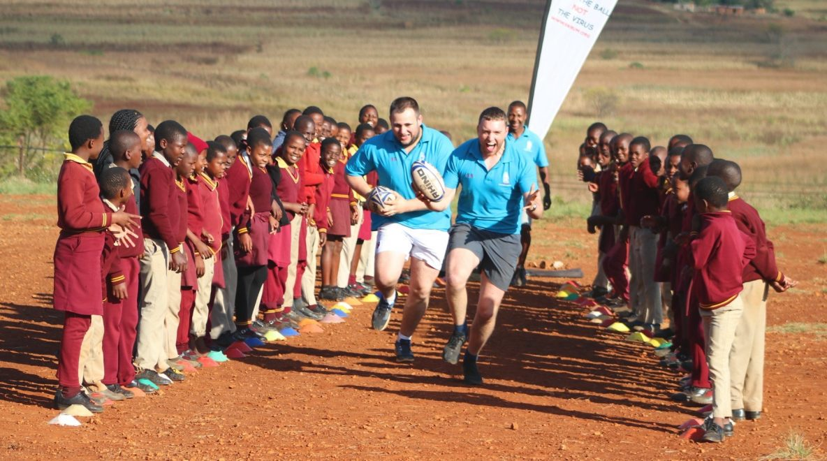 volunteers running with balls while Swazi kids watch on
