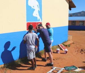 Painting sipho onto school wall