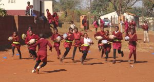 lots of girls in red uniform running with rugby balls