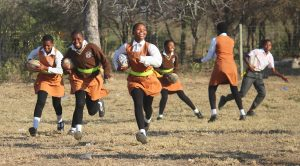 Girls playing rugby in orange and brown uniform